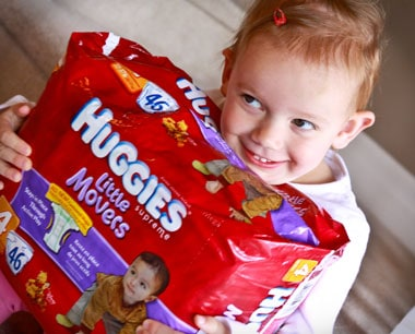 Olivia hugging a packing of Huggies Little Movers diapers