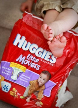 Toddlers feet resting on Huggies diapers