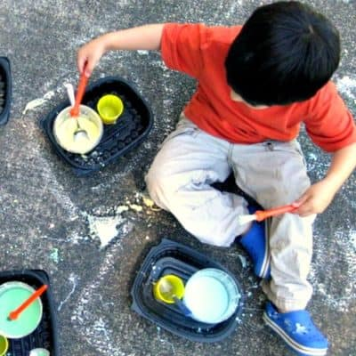 preschooler painting with sidewalk chalk