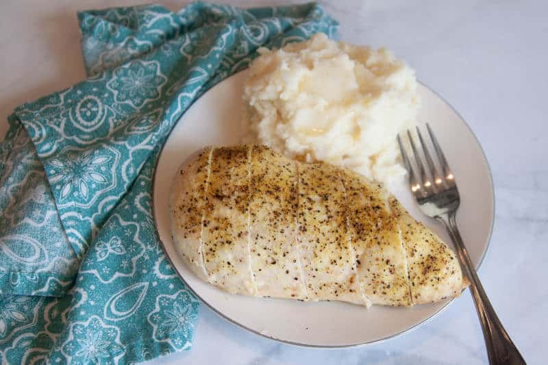 lemon pepper seasoning on chicken breast on white plate