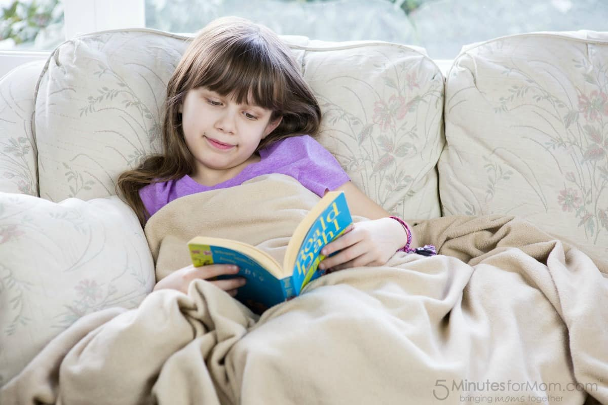 Sophia reading under a blanket