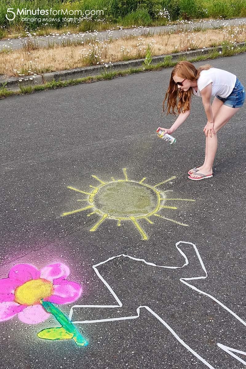 Teenage girl spray chalking sidewalk art