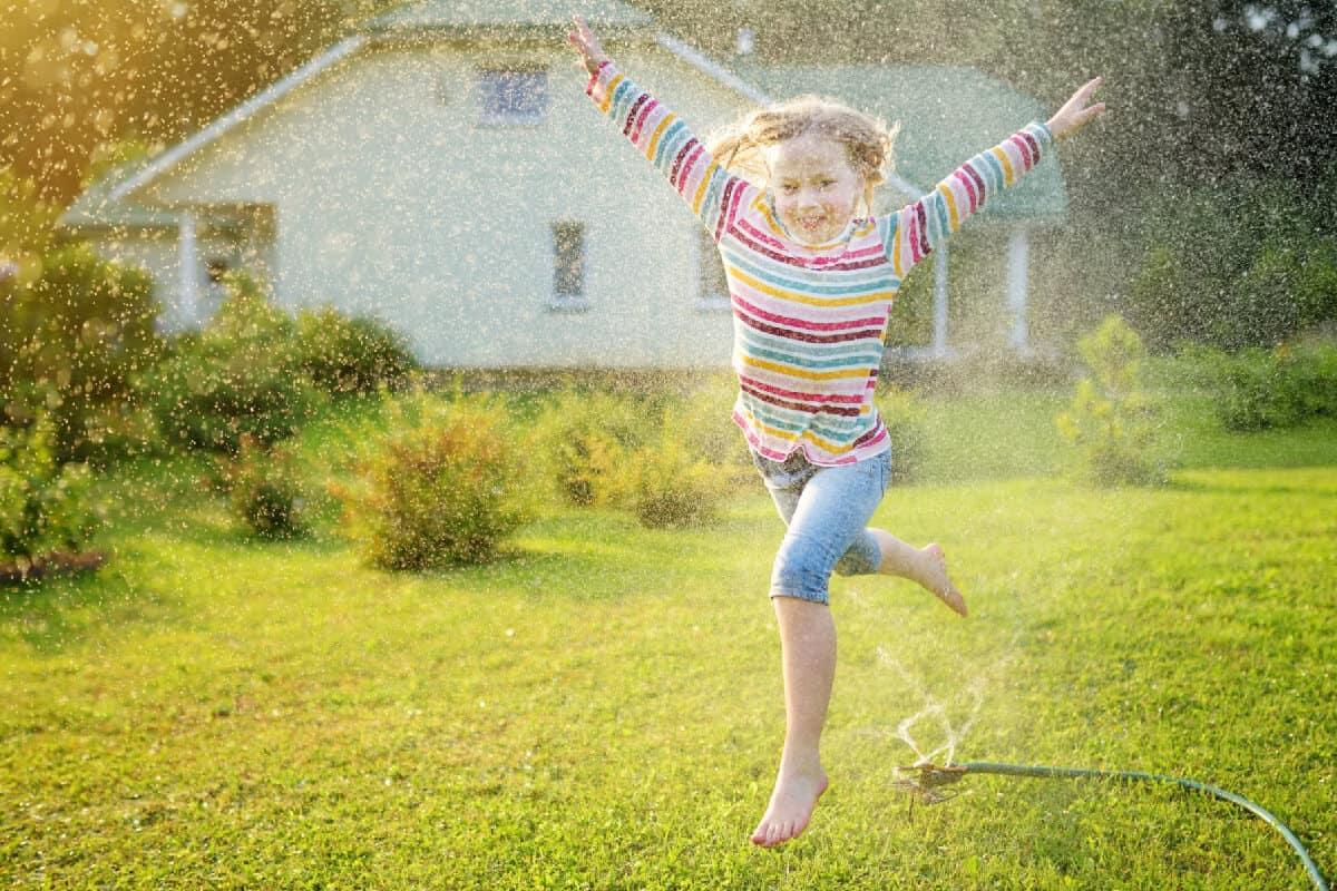 Summer Fun Running Through a Sprinkler