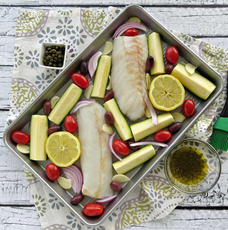 Mediterranean Cod Sheet Pan Dinner. Thinly slicing the garlic and quartering the zucchini ensures that they cook through in the same time as the fish.