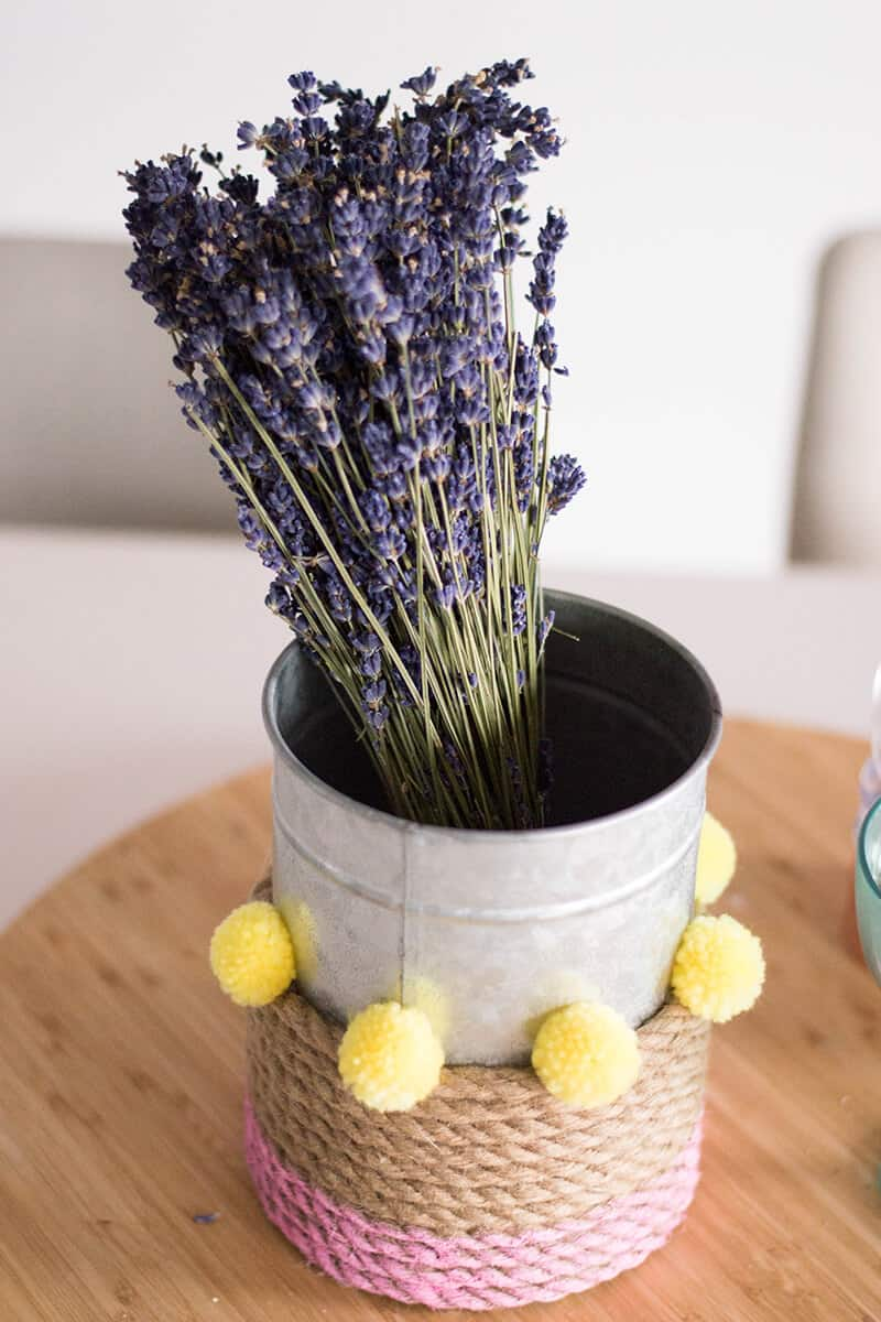 A Rope Vase DIY to add that touch of color to your home. How can you go wrong with pink, pompoms, and a bouquet of flowers?