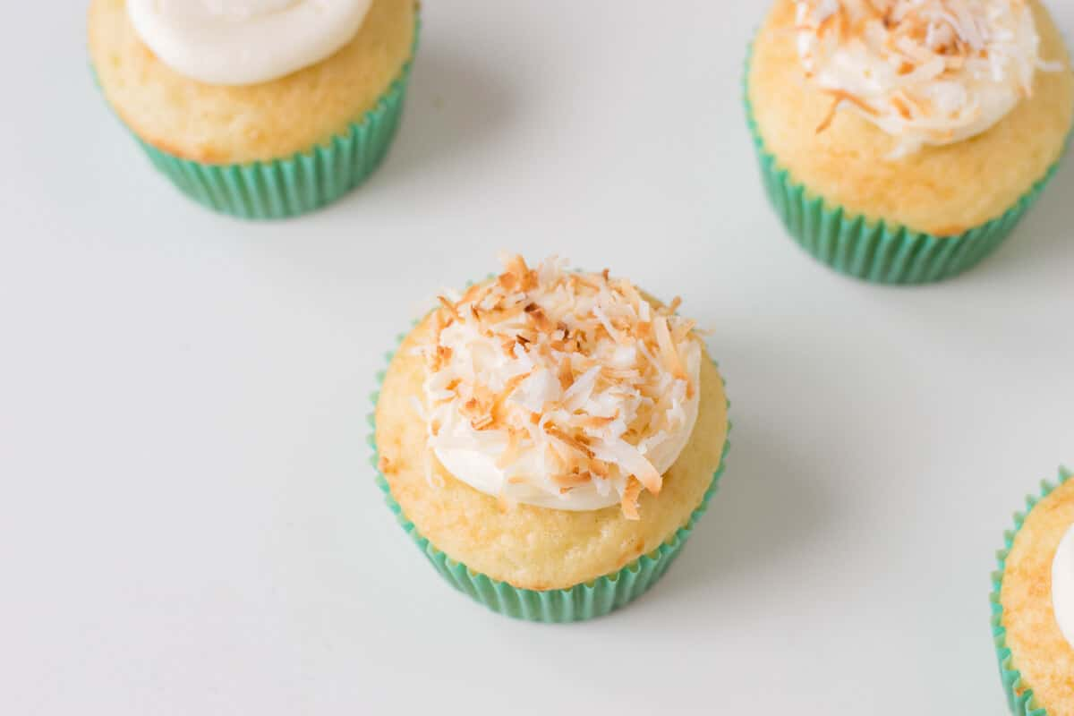 Adding coconut topping to vanilla cupcakes to make Bird's Nest Cupcakes.