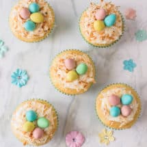 Vanilla cupcakes topped with buttercream, shredded coconut and candied eggs: they make for the perfect Bird's Nest Cupcakes!