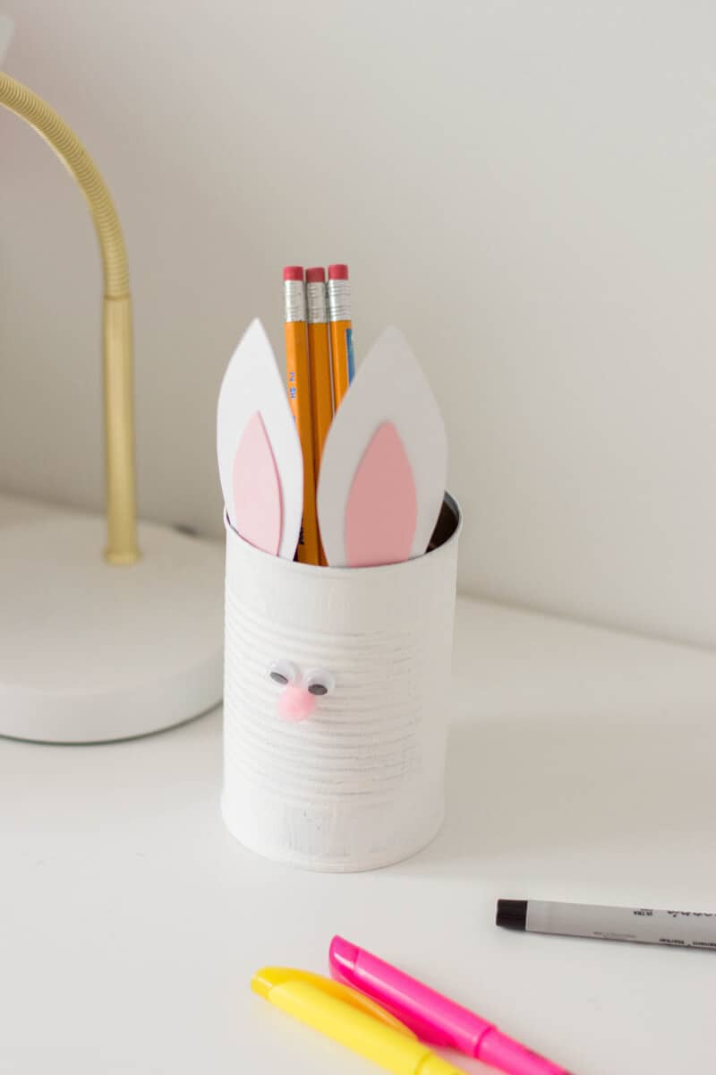 An Easter DIY made of a painted tin can with bunny ears and a pompom nose. Here's our very own Bunny Pencil Holder.