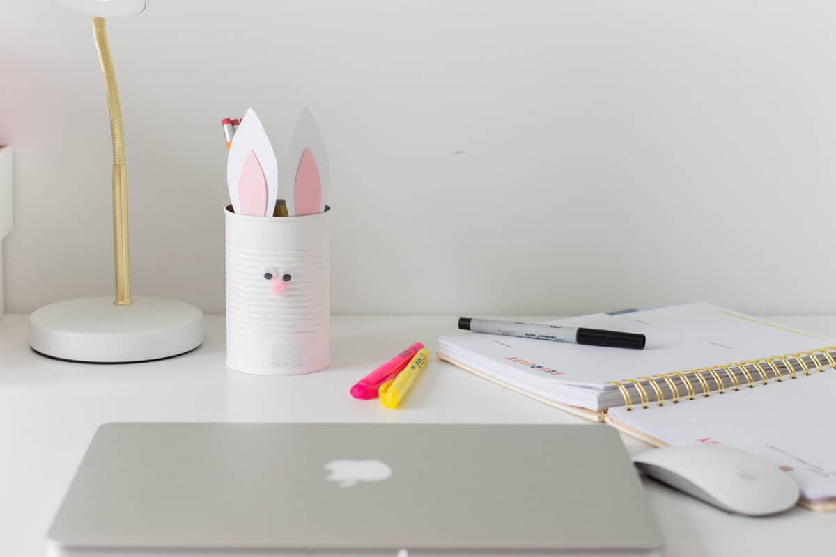 Easter Craft for Kids - Bunny Pencil Holder made of a painted tin can with bunny ears and a pompom nose.