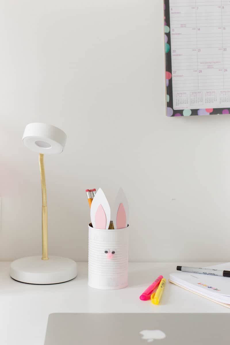 An easy Easter craft for kids. Use a painted tin can with bunny ears and a pompom nose to make a Bunny Pencil Holder.