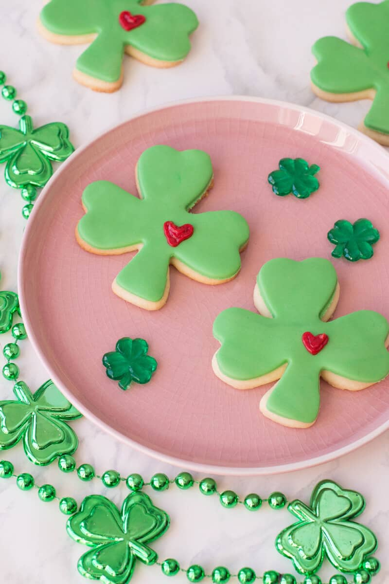 St Patricks Day Sugar Cookies shaped as lucky clovers with green fondant and a frosted heart.