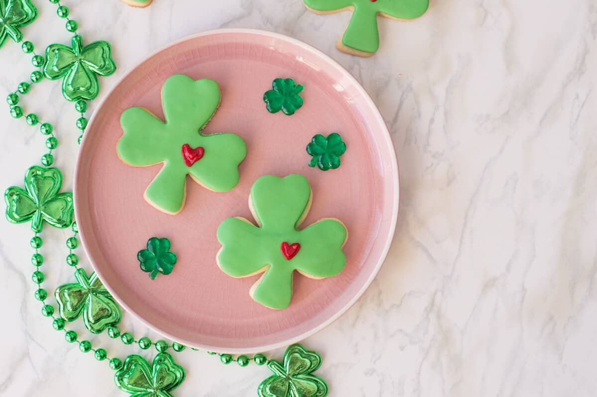 St. Patrick's Day Sugar Cookies shaped as lucky clovers with green fondant and a frosted heart.
