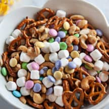 Spring snack mix in white bowl on a white marble background