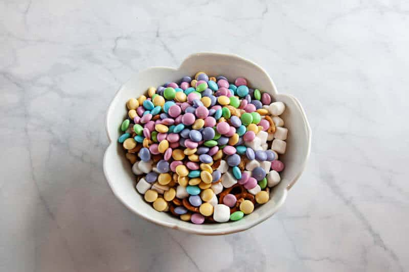 spring snack mix ingredients in clear bowls, and white bowl on white marble background