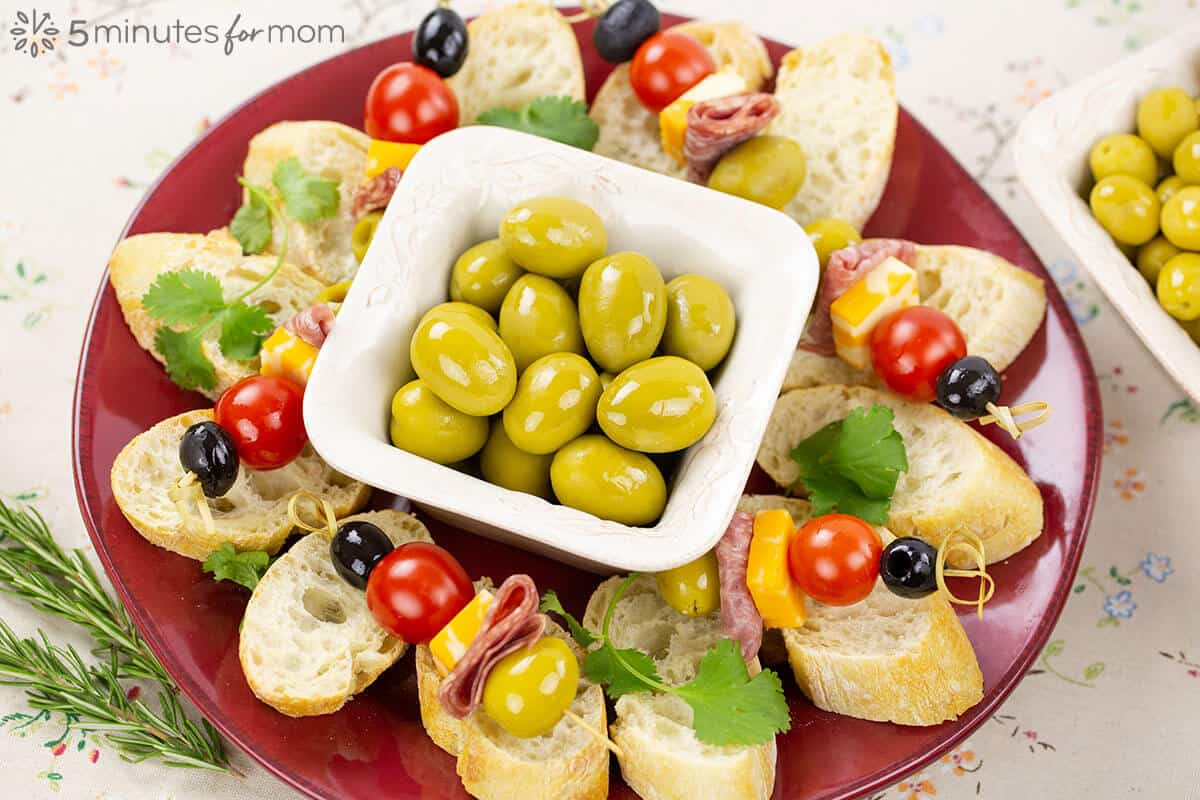 A platter filled with sliced baguette and skewers with European olives, cheese, tomatoes, and deli meat.
