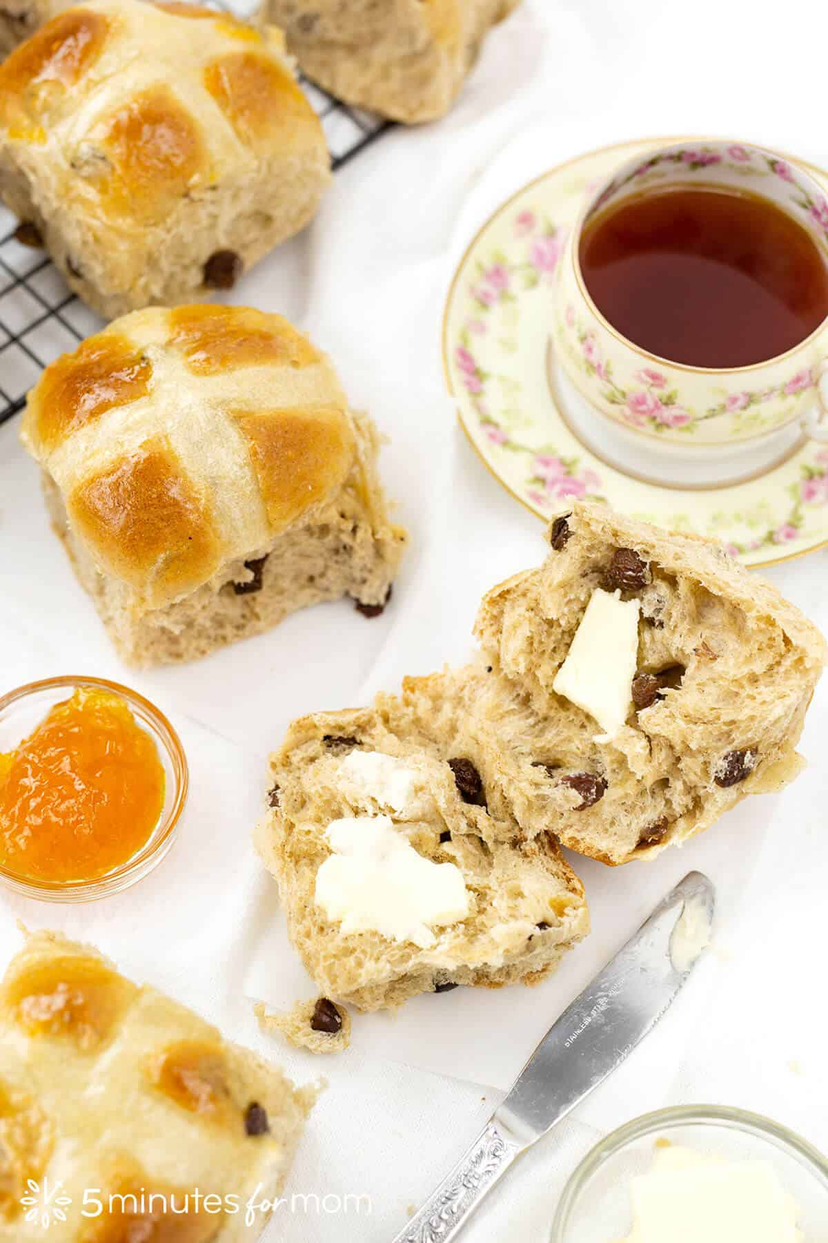 traditional hot cross buns served with butter and a cup of tea