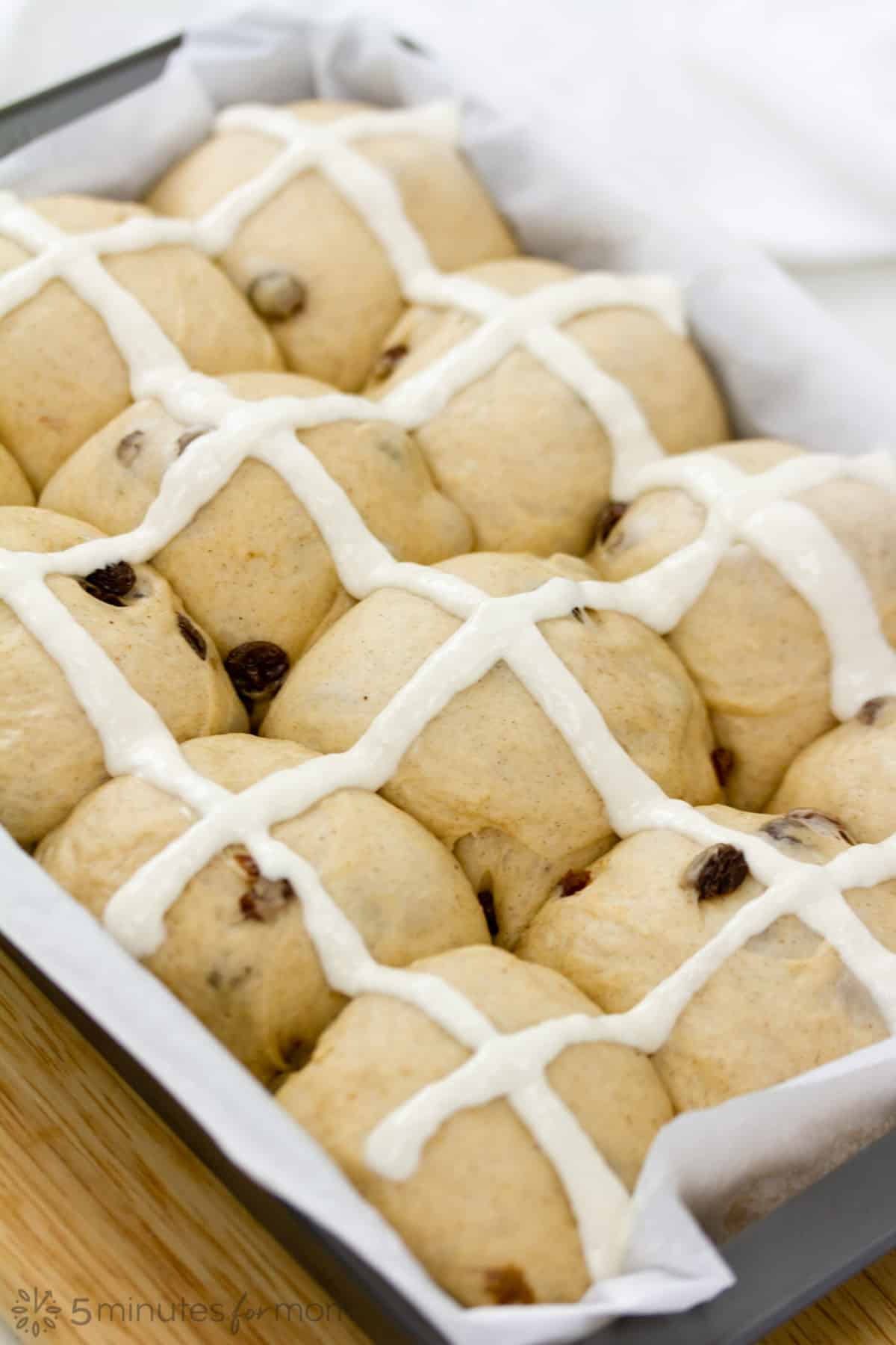 crosses made on hot cross buns with a flour and water paste piped in vertical and horizontal lines to create crosses on each bun