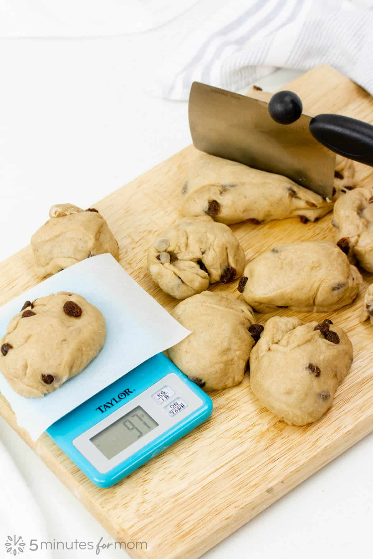 divide the dough in twelve and measure each portion with a kitchen scale for evenly baked buns