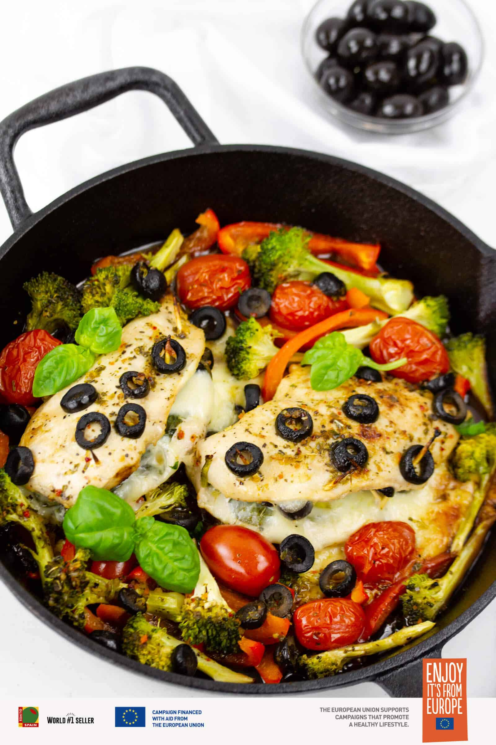 Stuffed chicken breasts with olives, tomatoes, and basil cooked in a cast iron pan.