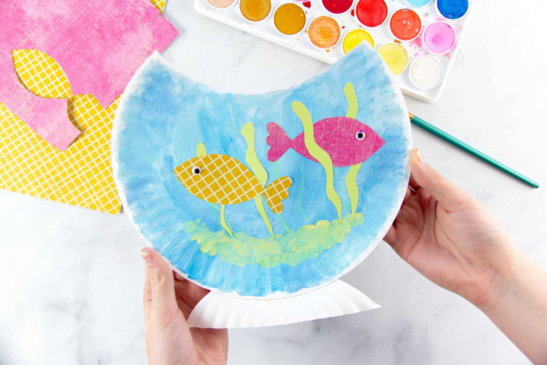 Hands holding a paper plate fish bowl craft