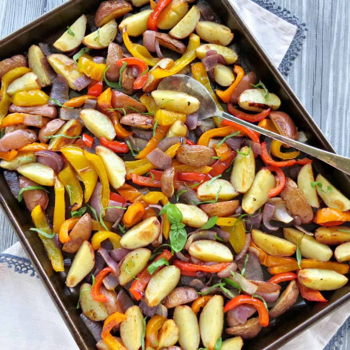baking sheet with oven roasted potatoes, peppers and onions with fresh basil